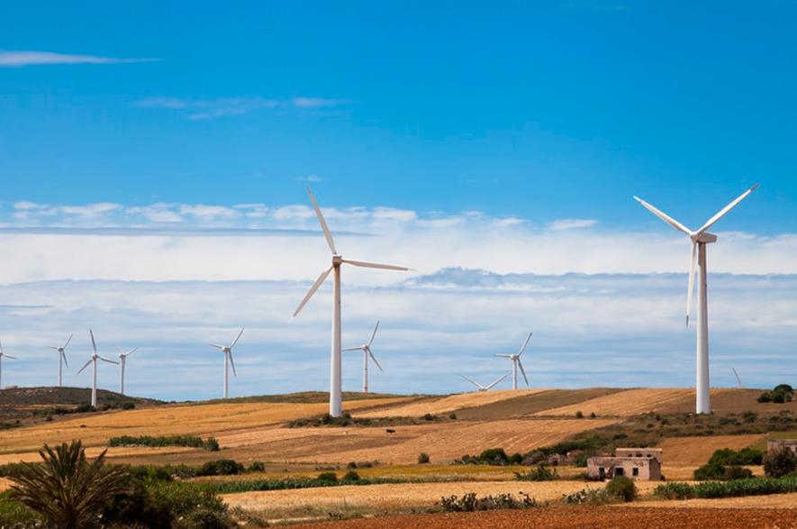 Várias turbinas eólicas em uma região rural e seca, com colinas